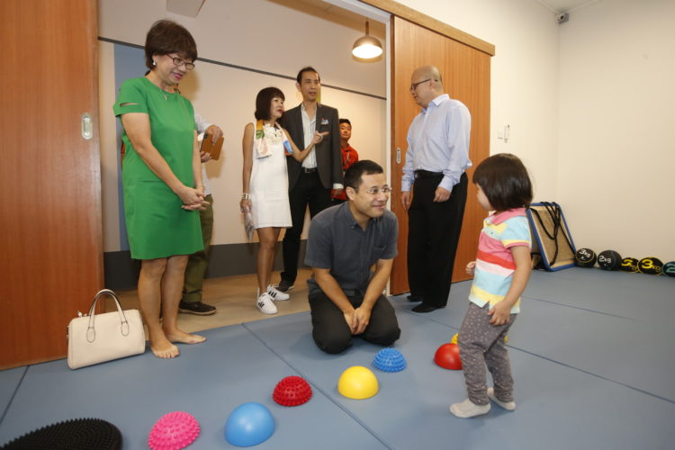 Minister Desmond Lee interacting with a child at ExtraOrdinary People Occupational Therapy Gym.